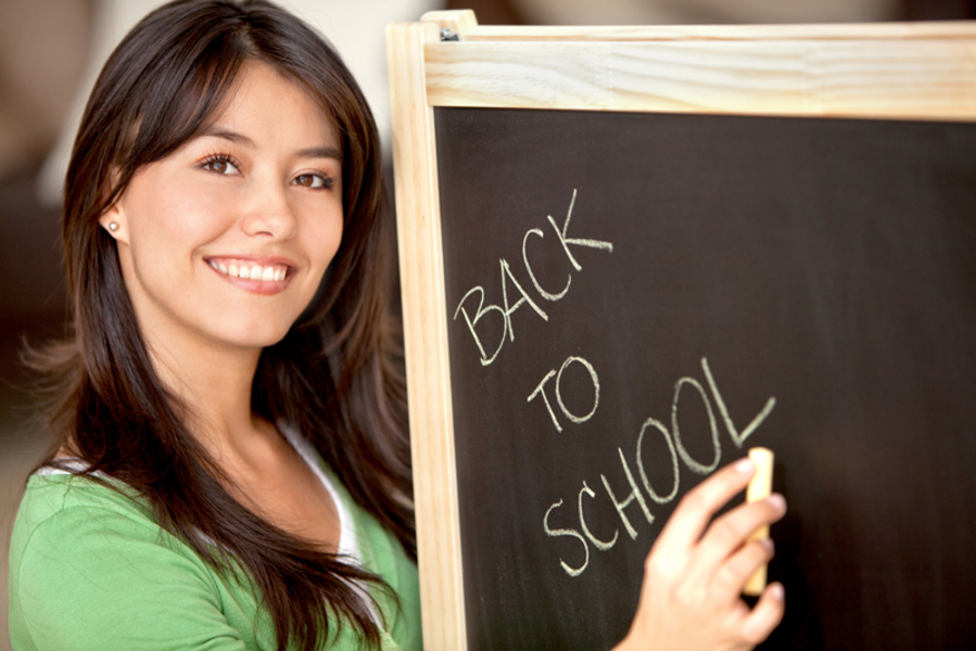Woman writing 'back to school' on a chalkboard